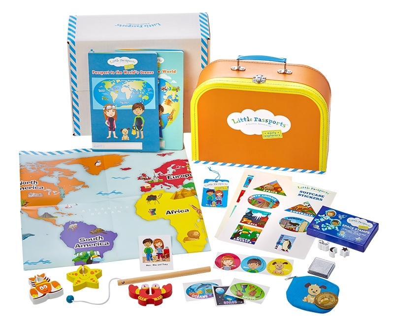 Little Passports box shown with a map, small suitcase, and kids play items displayed.